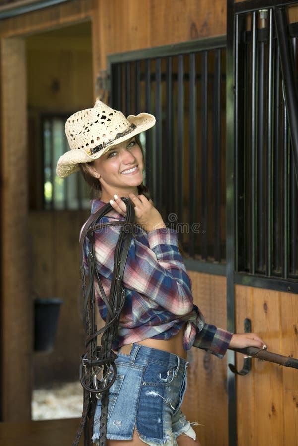 Den gulliga tonåriga flickan i dress för hästridning poserar i ladugård arkivfoto