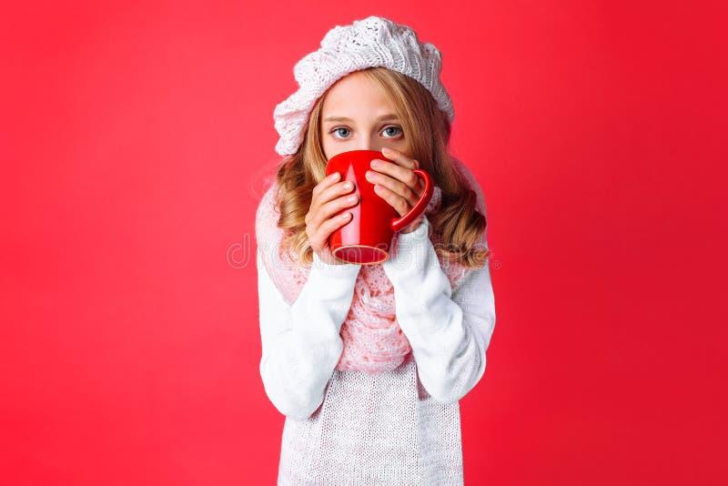 Den gulliga tonåriga flickan och att värma sig med en råna av te som är iklätt en rosa färg, stack hatten och halsduken, på en ro fotografering för bildbyråer