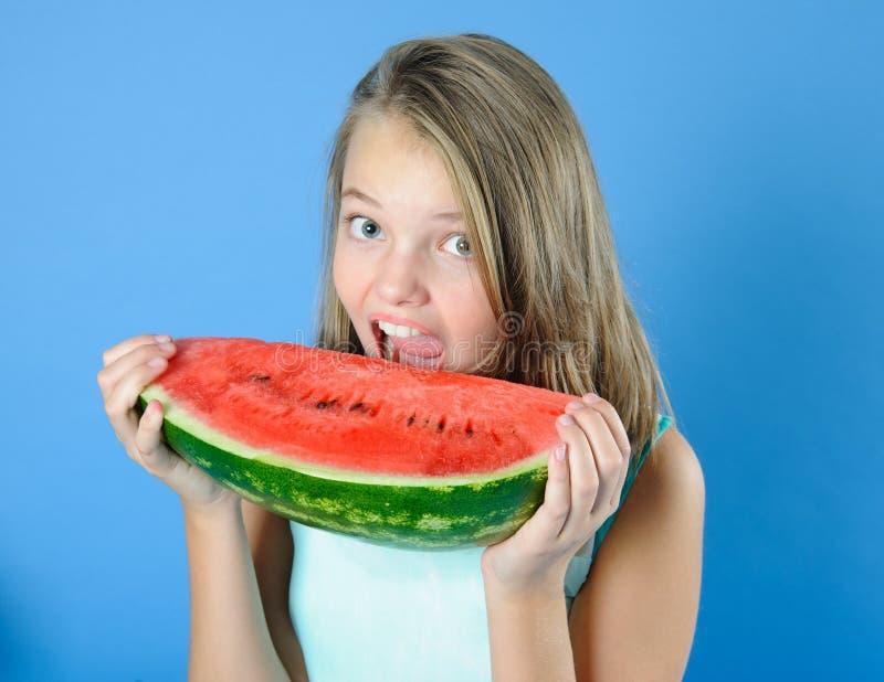 Den gulliga tonåriga flickan tar en tugga av vattenmelon royaltyfria foton