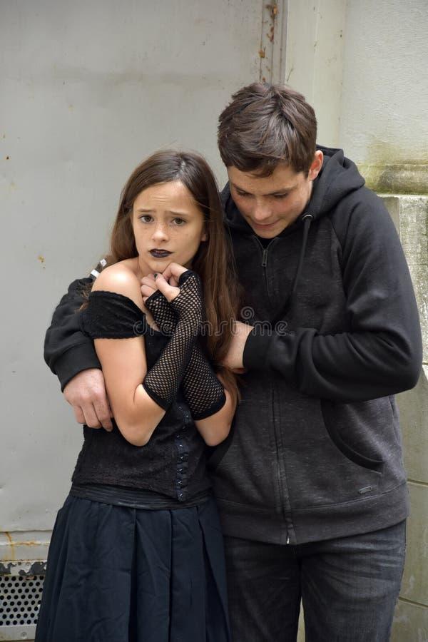 Den gulliga tonåringbrodern skyddar hans rädda lilla syster royaltyfria foton