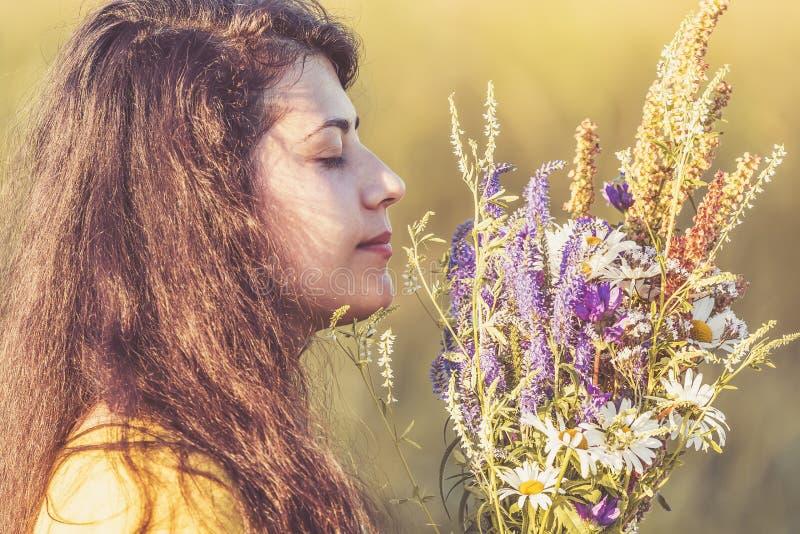 Den gulliga ung flickaståenden med fältet blommar under sommarsolnedgång tonad bild royaltyfri fotografi