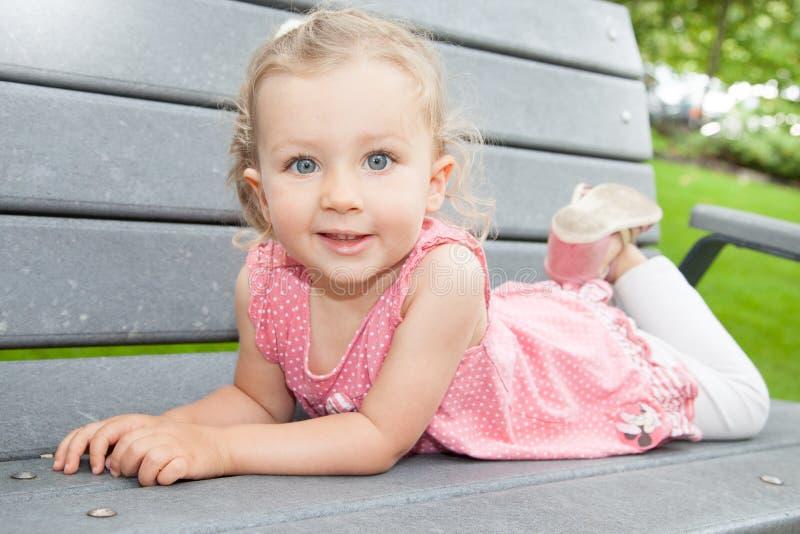 Den gulliga unga blonda flickan som ligger på den wood bänken parkerar in arkivfoto
