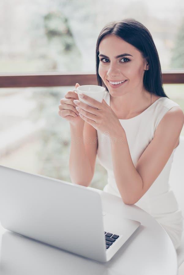 Den gulliga unga brunetten har te på kafét Hon är lycklig, smi arkivfoton