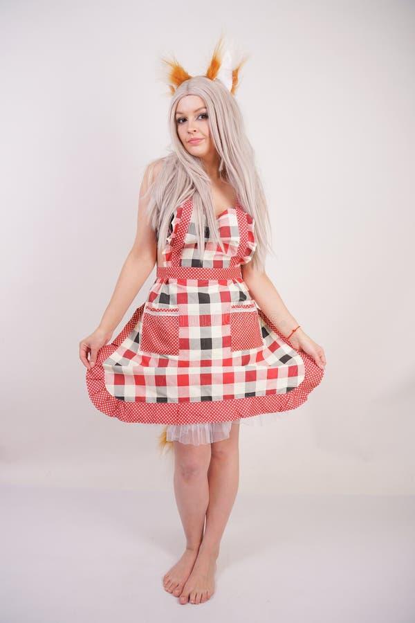 Den gulliga unga caucasian flickan i kökplädförkläde med fluffiga rävöron och pälsfodrar länge den röda svansen som barfota står  arkivfoton