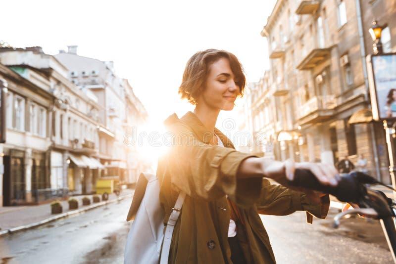 Den gulliga unga fantastiska kvinnan som utomhus går parkerar in, med härlig vårdag för cykel royaltyfri fotografi