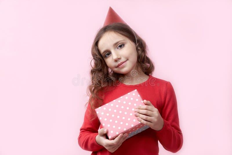 Den gulliga unga flickan i rött födelsedaglock rymmer för henne en gåvaask med lyckligt glat uttryck och leende fotografering för bildbyråer