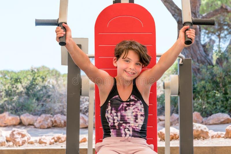 Den gulliga unga flickan som övar armar, och bröstkorgen på idrottshall bearbetar med maskin utomhus arkivbilder