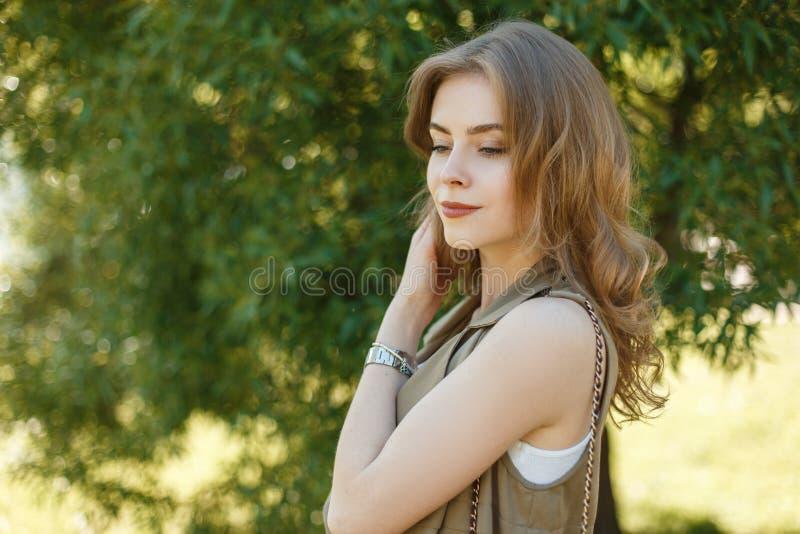 Den gulliga unga kvinnan i en trendig sommar tilldelar en stilfull vit T-tröja som utomhus poserar i, parkerar fotografering för bildbyråer