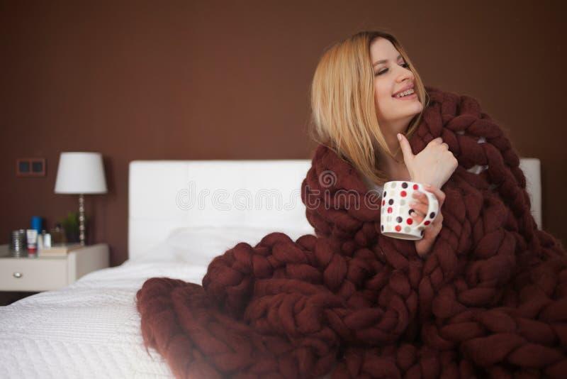 Den gulliga unga kvinnan sitter på sängen som slås in i en stor och fluffig brun pläd Härlig flicka i en hemtrevlig filt royaltyfri bild