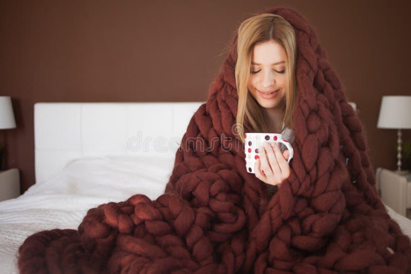 Den gulliga unga kvinnan sitter p? s?ngen som sl?s in i en stor och fluffig brun pl?d H?rlig flicka i en hemtrevlig filt arkivfoto