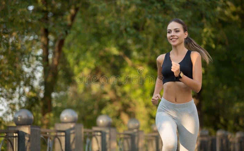 Den gulliga unga kvinnan som in joggar, parkerar, fritt utrymme royaltyfria bilder