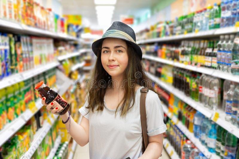 Den gulliga unga kvinnan v?ljer en flaska av fruktsaft i supermarket ton arkivbilder