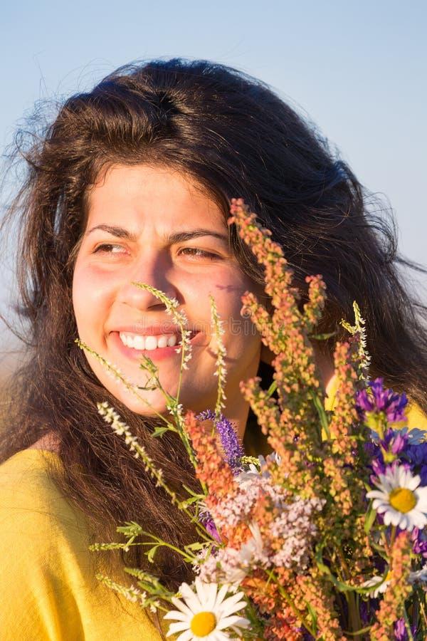 Den gulliga unga le flickaståenden med fältet blommar under sommarsolnedgång arkivbilder