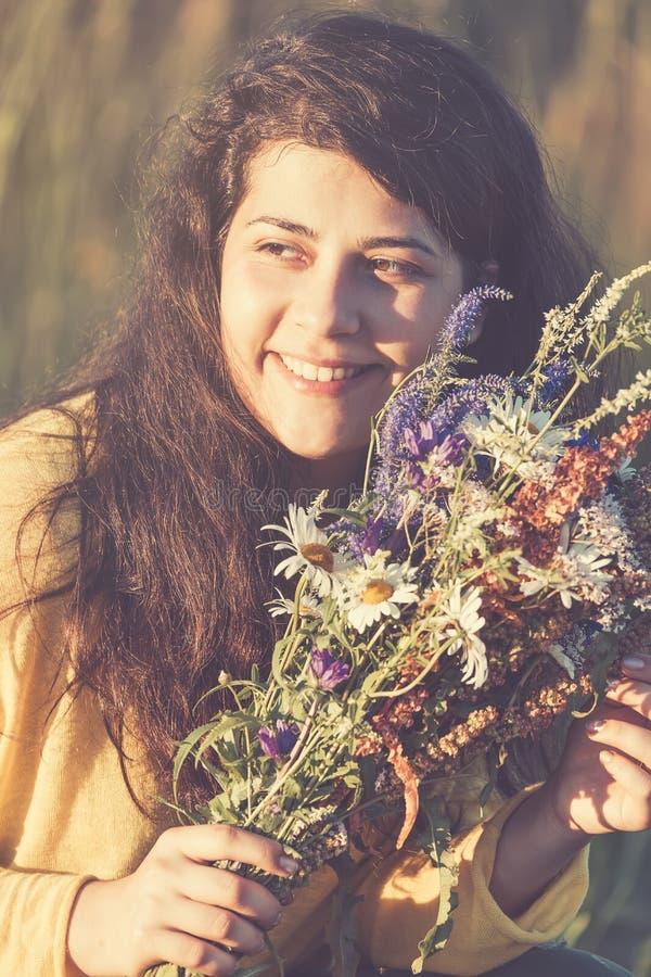 Den gulliga unga le flickaståenden med fältet blommar under sommarsolnedgång tonad bild arkivfoton