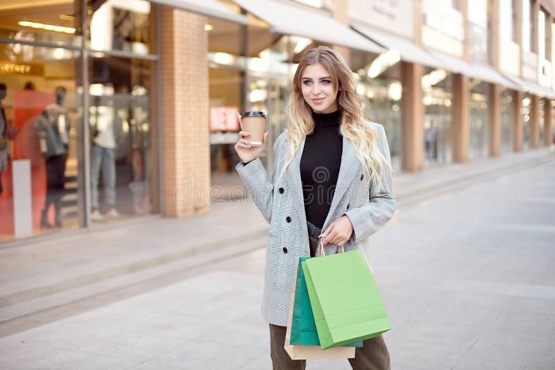 Den gulliga unga modekvinnan med shoppa påsar som står nära skyltfönster, shoppar fönster på gatan utomhus royaltyfri bild
