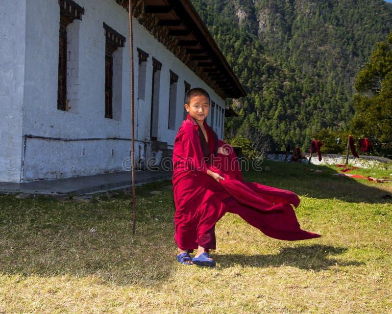 Den gulliga unga novismunken lät hans ämbetsdräkt som fladdrar i vinden, östliga Bhutan royaltyfri foto