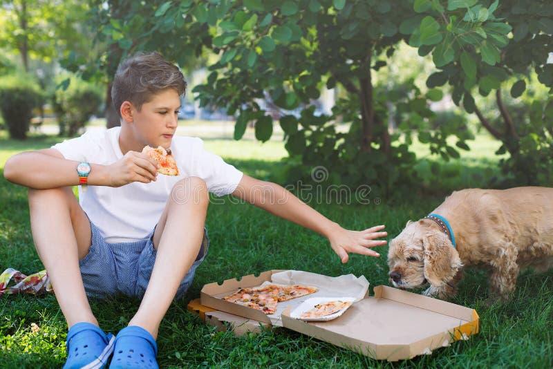 Den gulliga unga pojken i den vita t-skjortan sitter på gräset och tar en skiva av pizza i sommaren parkerar Pojken äter pizza arkivbilder