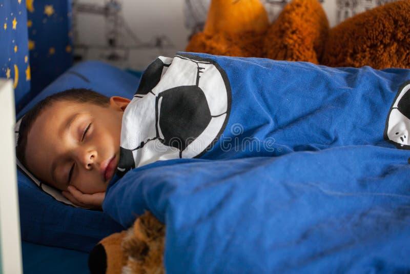 Den gulliga unga pojken sover med taddy i hans säng royaltyfri foto