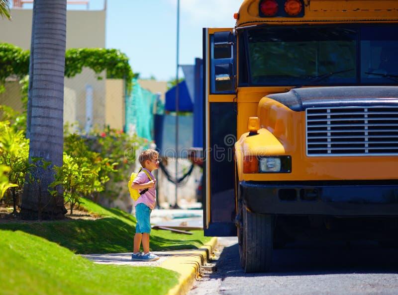 Den gulliga unga pojken, ungen som får på skolbussen, ordnar till för att gå till skolan royaltyfri fotografi