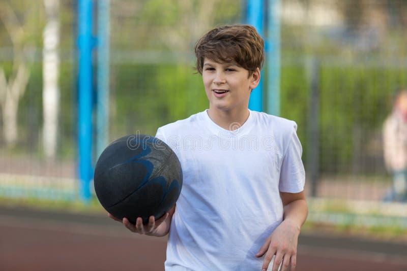 Den gulliga unga sportiga pojken i den vita t-skjortan spelar basket på hans fria tid, ferier, sommardag på sportjordningen sport royaltyfri bild