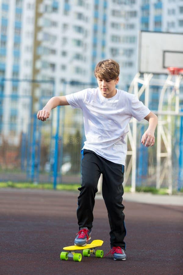 Den gulliga unga sportpojken som åker skridskor på den gula skateboarden och, har en bra tid på hans fria tid på helg, semestrar  arkivfoto