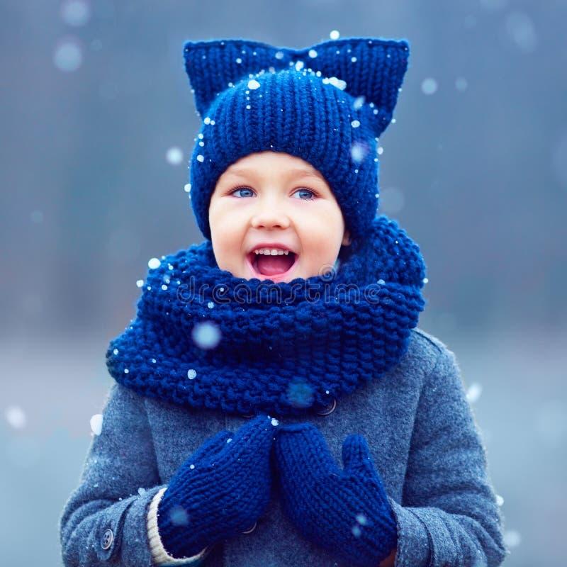 Den gulliga ungen, pojke i vinter beklär att spela under snön royaltyfri foto