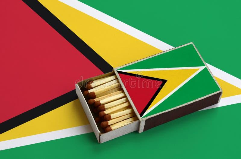 Den Guyana flaggan visas i en öppen tändsticksask, som fylls med matcher och ligger på en stor flagga royaltyfria bilder