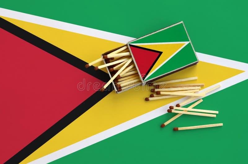 Den Guyana flaggan visas på en öppen tändsticksask, som flera matcher faller från och lögner på en stor flagga royaltyfri bild