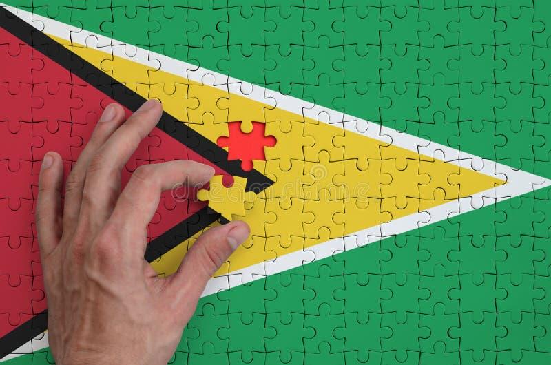 Den Guyana flaggan visas på ett pussel, som handen för man` s avslutar för att vika arkivbild