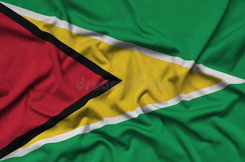 Den Guyana flaggan visas på ett sporttorkduketyg med många veck Baner för sportlag arkivfoto