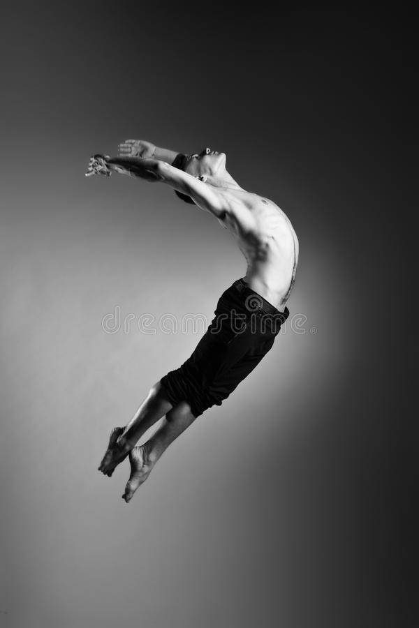 Den gymnastiska Caucasian mannen hoppar ställing på grå färger royaltyfria bilder