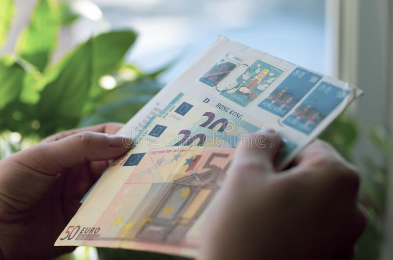 In den Händen der Frauen ein Papierumschlag und Eurobanknoten lizenzfreies stockbild