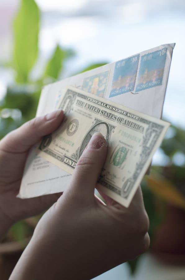 In den Händen der Frauen ein Umschlag mit Stempel von Hong Kong und von Dollar stockbild