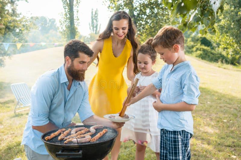 Den hängivna faderportionsonen som använder trätång under familjen, har picknick royaltyfria foton