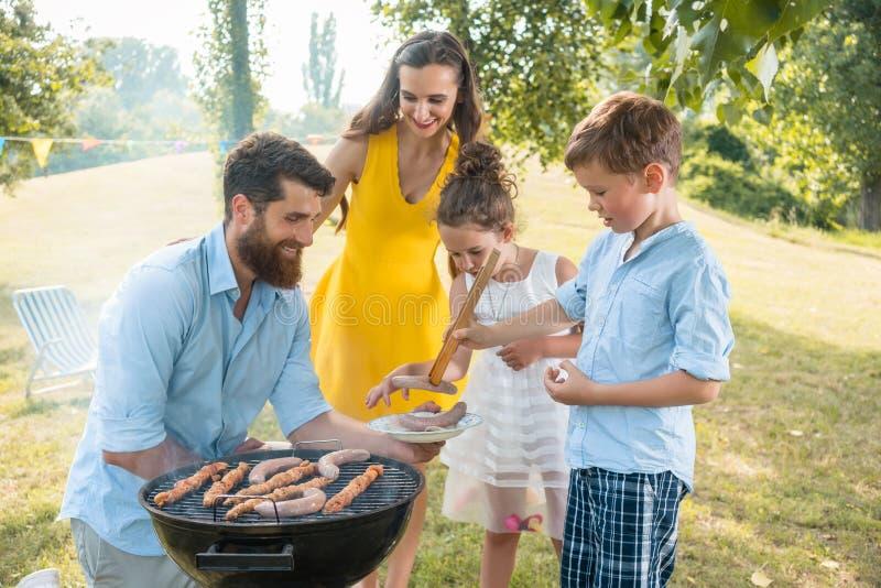 Den hängivna faderportionsonen som använder trätång under familjen, har picknick royaltyfri fotografi