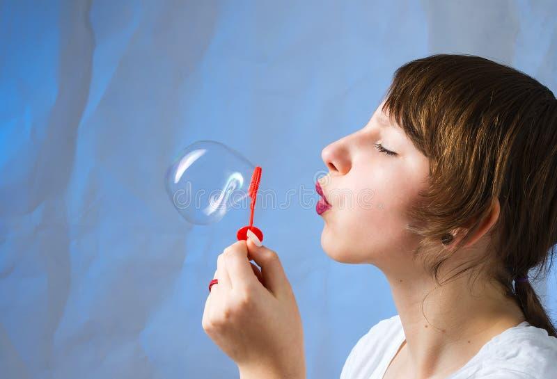 Den härliga älskvärda flickan blåser såpbubblor royaltyfria bilder