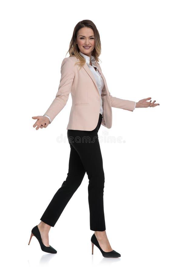 Den härliga affärskvinnan går för att sid och gör inviterande gest arkivbild