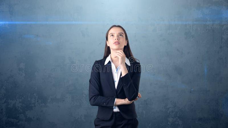 Den härliga affärskvinnan med armar vek att se upp på copyspace Stå över grå bakgrund arkivfoto