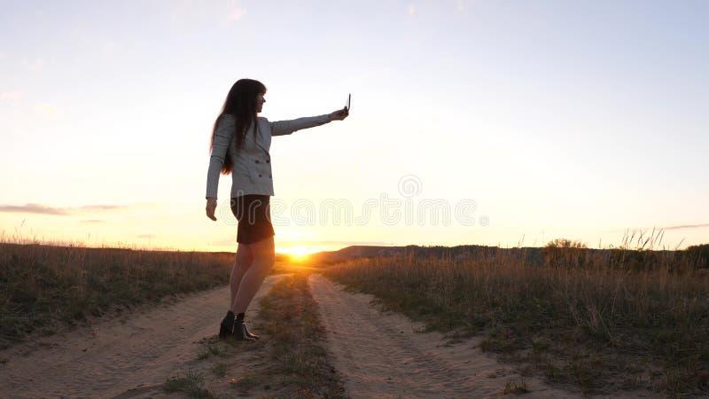 Den härliga affärskvinnan reser och tar ett selfiefoto genom att använda en mobil smartphone på vägen mot solnedgången arkivfoto