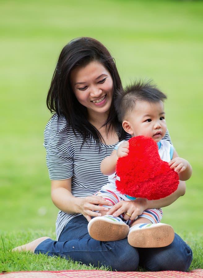 Den härliga asia modern och behandla som ett barn royaltyfria bilder