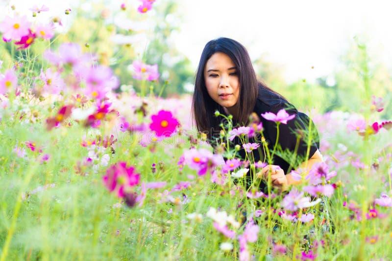 Den härliga asiatet kopplar av lyckligt le för kvinnor i rosa kosmosblomma fotografering för bildbyråer