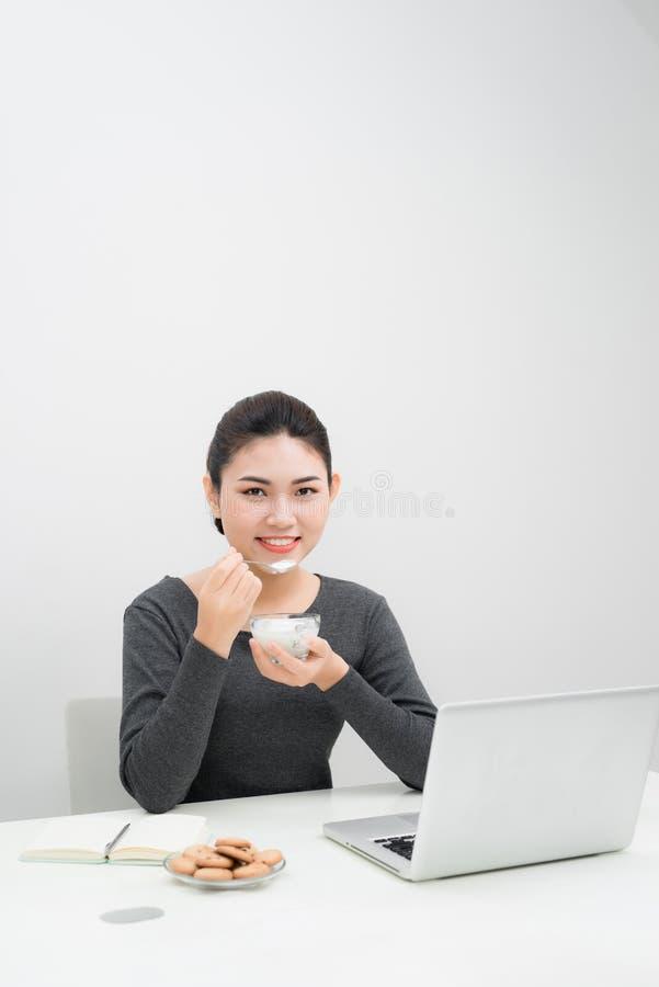 Den härliga asiatiska affärskvinnan äter yoghurt och ler whil arkivbild
