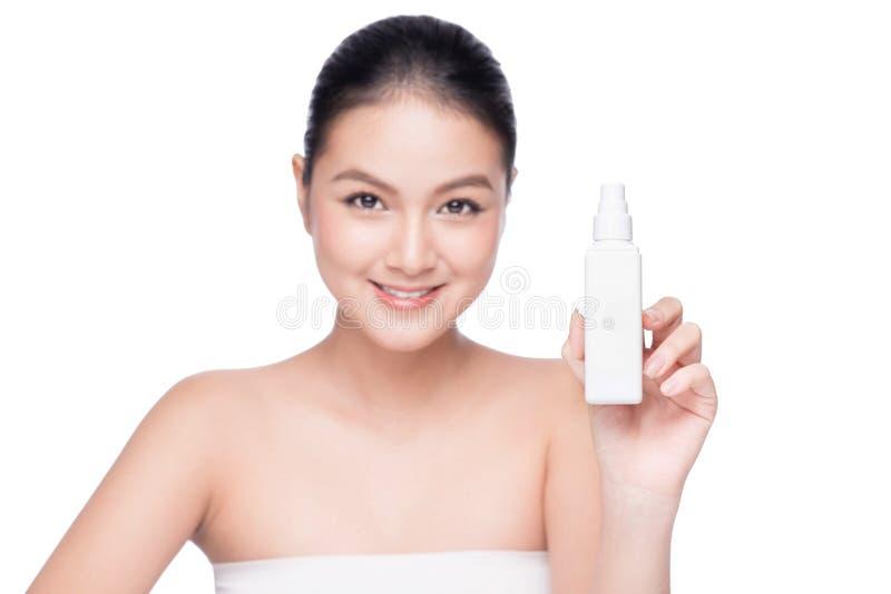 Den härliga asiatiska flaskan för vatten för kvinnainnehavsprej isolerade vit royaltyfri fotografi