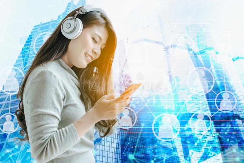 Den härliga asiatiska flickan arbetar på smartphonen och lyssnar till M arkivfoton
