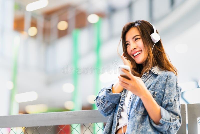 Den härliga asiatiska flickan lyssnar till musik genom att använda smartphone- och headphoneleende på kopieringsutrymme, hobbyen  royaltyfri bild