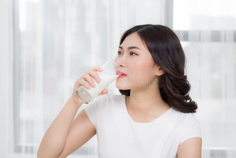 Den härliga asiatiska flickan som dricker ett exponeringsglas av, mjölkar fotografering för bildbyråer