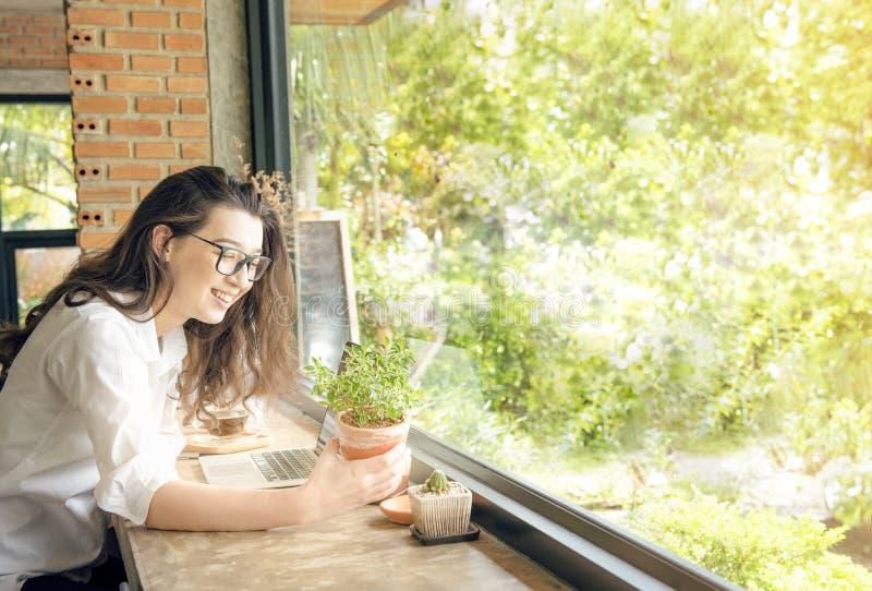 Den härliga asiatiska krukan för växten för flickahandhållen med lyckligt poserar E-kommers, universitetutbildning, internettekno royaltyfria bilder