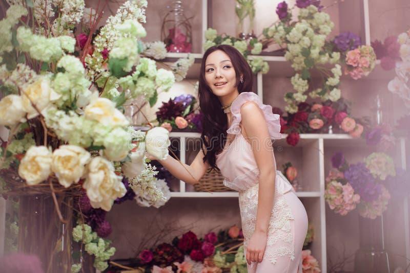 Den härliga asiatiska kvinnablomsterhandlaren i rosa färger klär i blommalager royaltyfria foton