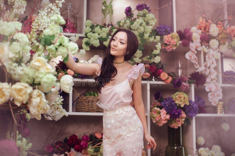 Den härliga asiatiska kvinnablomsterhandlaren i rosa färger klär i blommalager arkivfoto