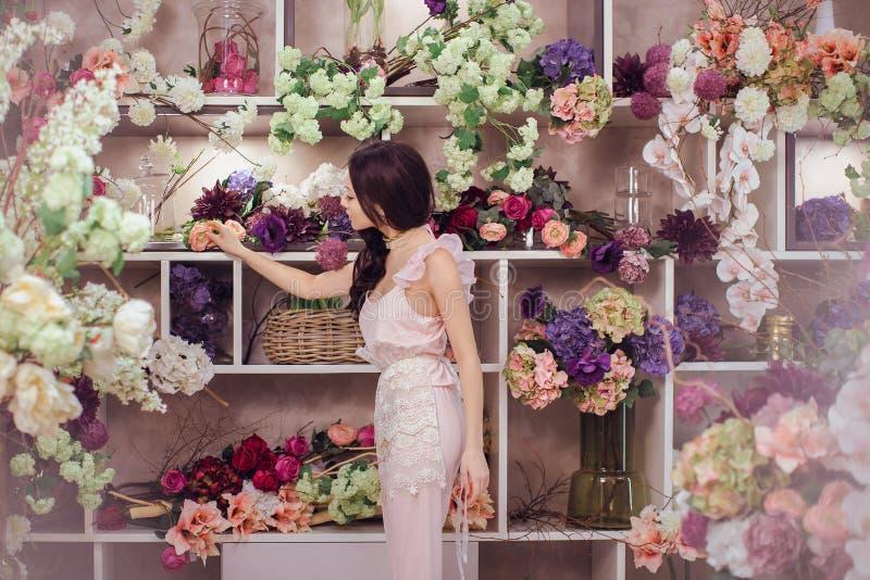 Den härliga asiatiska kvinnablomsterhandlaren i rosa färger klär i blommalager royaltyfria bilder